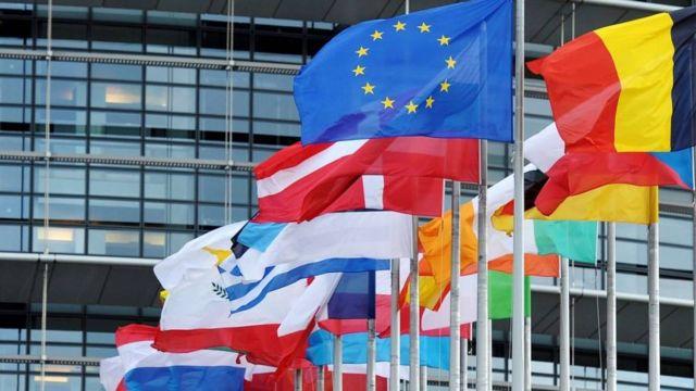 Bandeiras de vários países da União Europeia em frente a prédio