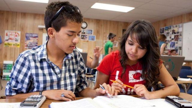 Dois adolescentes sentados lado a lado escrevem em uma caderno