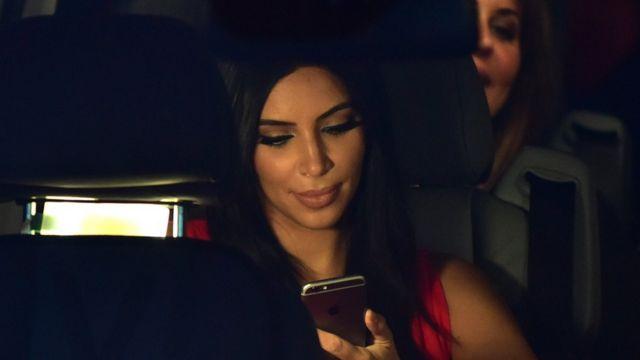 Kim Kardashian con su celular en un auto