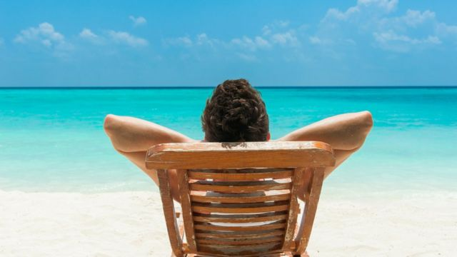 Hombre acostado en silla de extensión en la playa