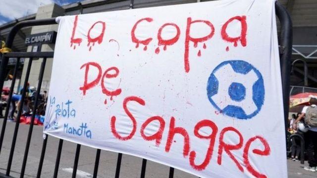 Protesto na Argentina> cartaz com dizeres em vermelho 'Copa de sangue'