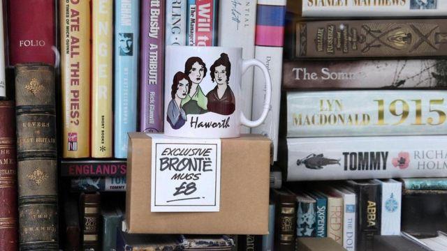 Libros y taza con las figuras de las hermanas Brontë