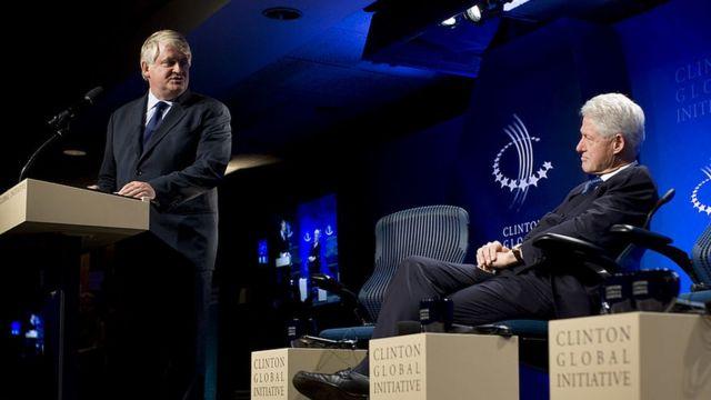 Bill Clinton escucha a Dennis O'Brien, director de Digicel mientras da su discurso en un evento de Iniciativa Global Clinton.