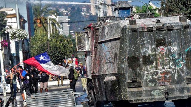 Un manifestante protestando con la bandera chilena junto a un carro lanza agua.