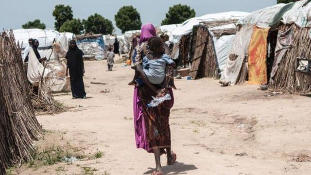 امرأة تسير في معسكر بدائي تحمل طفلا