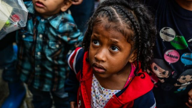 Children wait for food in soup kitchens that provides free food in Caracas on 5 November 2017