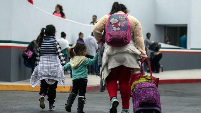 Inmigrantes caminando hacia el puerto de entrada de El Chaparral en Tijuana, México, en la frontera con Estados Unidos
