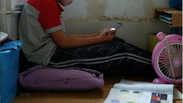 Criança fazendo aula pelo celular