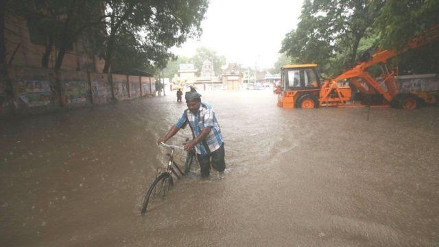 رجل يجر دراجة وسط مياه تغمر الشارع