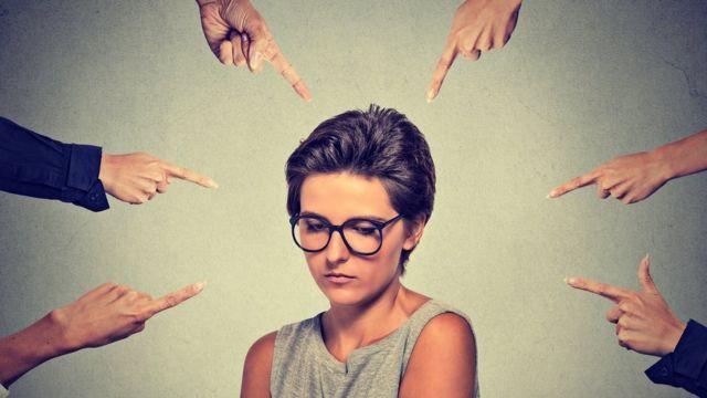 Mulher com diversos dedos apontados para ela