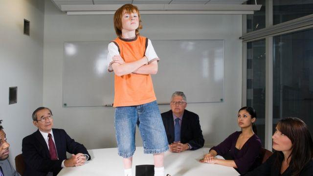 Un niño de pie sobre la mesa de una junta de directivos.