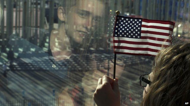 Girl with US flag and reflection of boy in window as they watch ceremony to mark reopening of US embassy in Havana