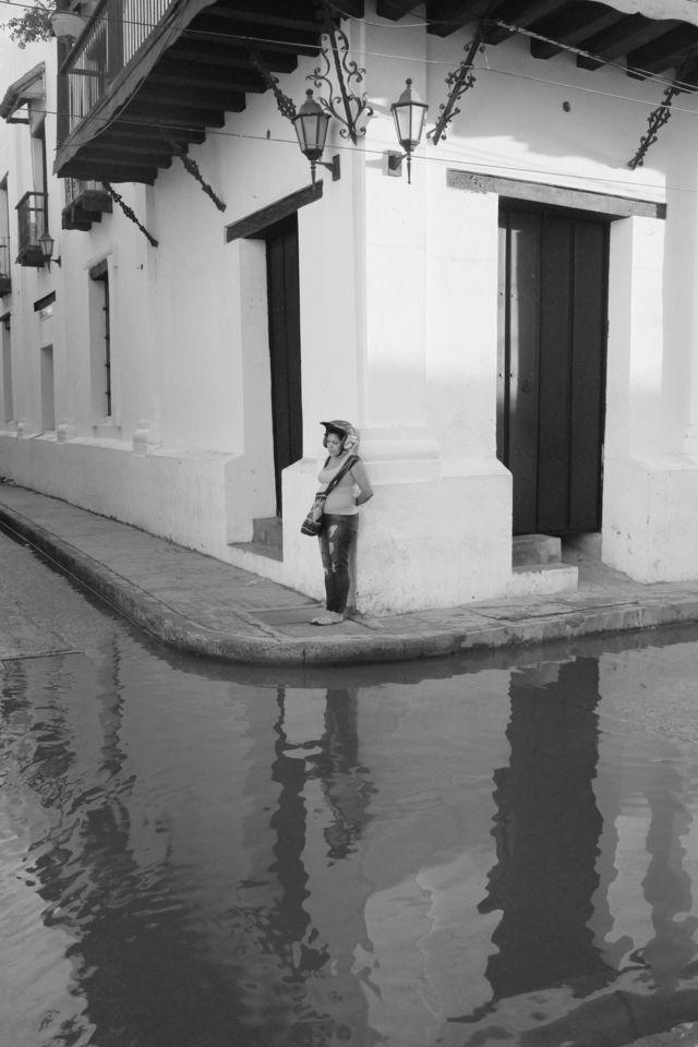 Mujer esperando en una esquina inundada tras una lluvia y su reflejo en el agua.