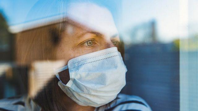 Mujer con mascarilla mirando con nostalgia por una ventana