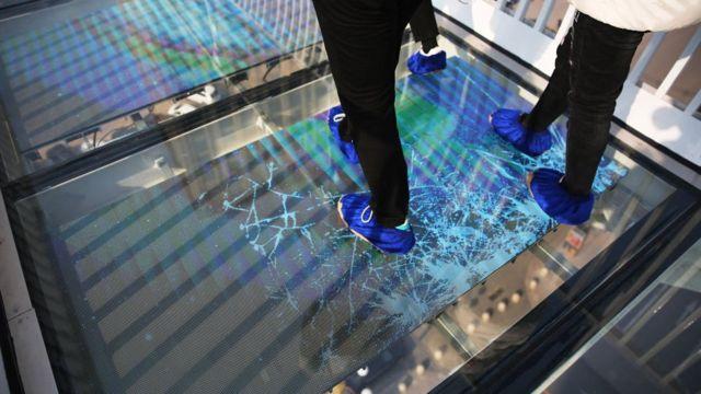 Pés de uma pessoa sobre ponte de vidro com efeito visual mostrando rachado