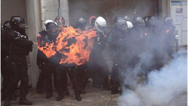 أفراد من شرطة مكافحة الشغب الفرنسية والنيران تحيط بهم خلال اشتباكهم مع المحتجين