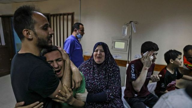 أحد أفراد عائلة أبو داير، محاطا بأقارب له، يبكي في مستشفى الشفاء بعد وفاة والده وابن عمه في غارة جوية إسرائيلية على منزل العائلة في مدينة غزة في 17 مايو/أيار 2021