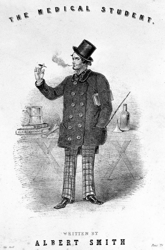 19. yüzyılda tasvir edilen bir tıp öğrencisi: bir maşrapa ile sigara içmek ve masanın üzerinde bir anatomi kitabı