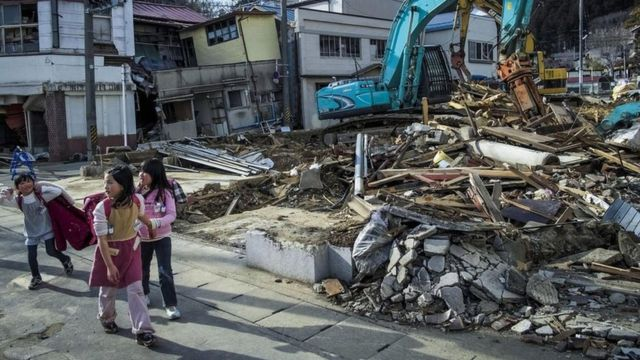 Girls walk in front of rubble in Fukushima area