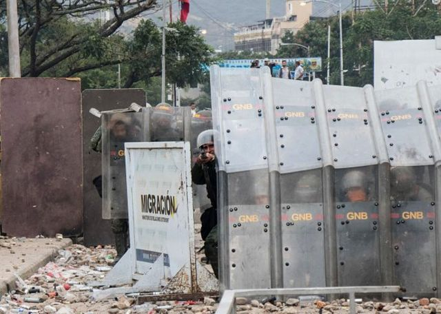 Pengunjuk rasa melempar batu ke arah pasukan keamanan Venezuela yang memblokade jembatan internasional Francisco de Paula Santander, yang menghubungkan Venezuela dan Kolombia.