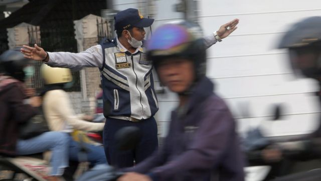 An Indonesian traffic officer directs traffic in Jakarta