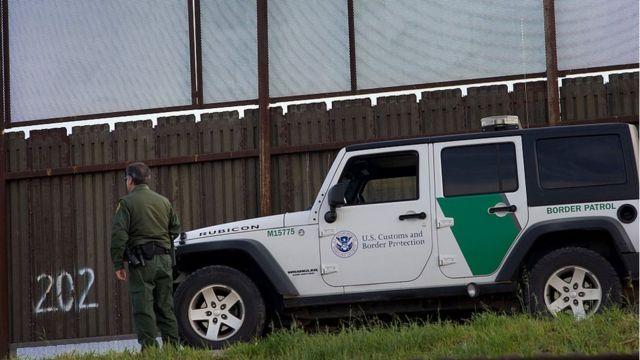 Un guardia de Estados Unidos junto a una valla en la frontera con México.