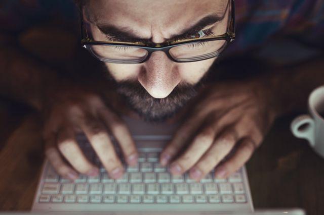 Hombre mirando una pantalla de computador