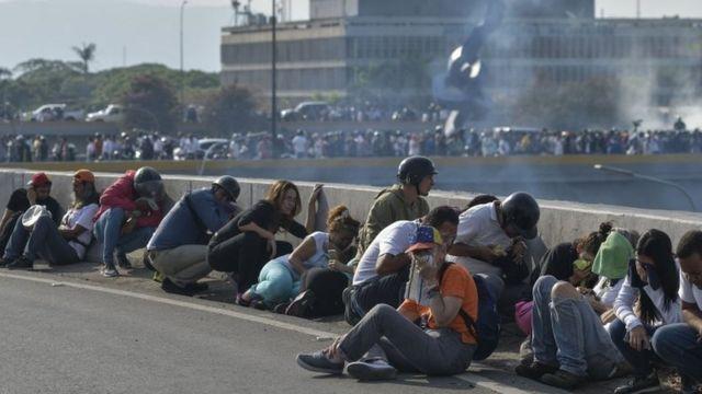 Pessoas agachadas na rua em Caracas em meio a confronto