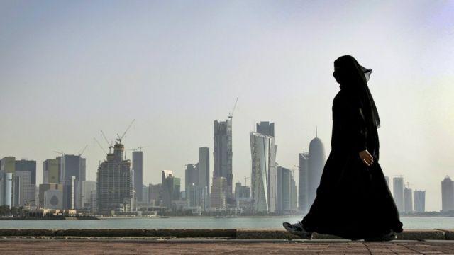 Mulher, vestida com burca, caminha em Doha