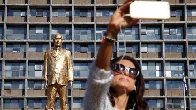 امرأة تلتقط صورة مع التمثال
