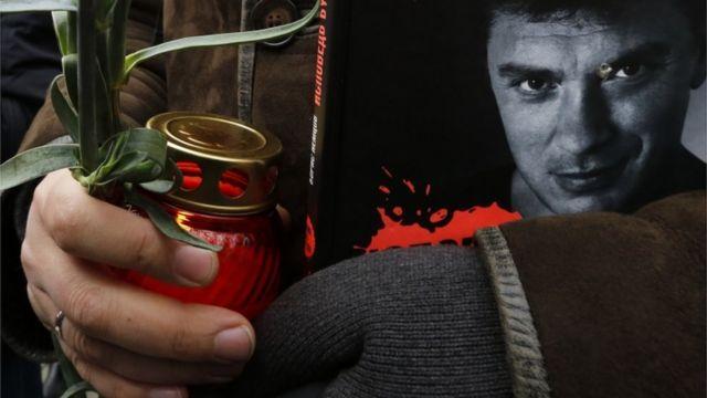 Boris Nemtsov fotoğrafı basılı bir dergi ve mum taşıyan bir Rus