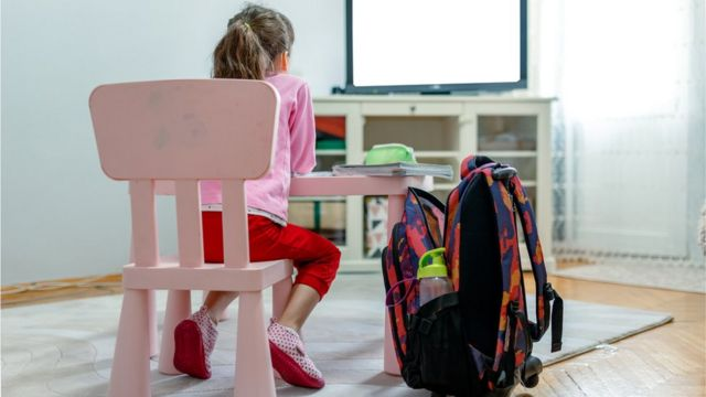 Em casa, menina sentada diante de mesa e TV, com mochila ao lado
