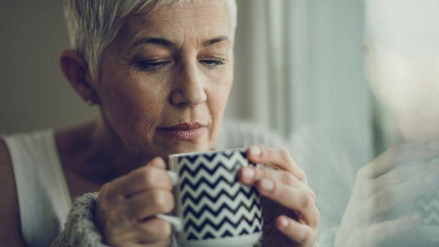 Mujer que huele y está por probar el contenido de una taza.