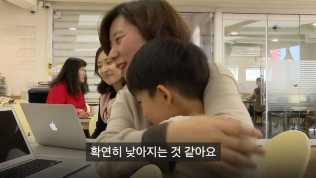 Mother hugs her son at the Ginger Tea Project in Seoul.