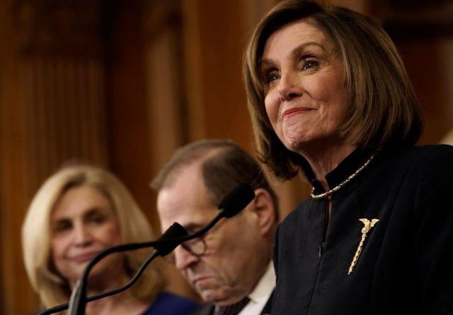 Chủ tịch Hạ viện Nancy Pelosi (phải) tươi cười trong ngày Hạ viện bỏ phiếu luận tội ông Trump