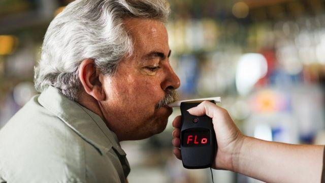 Hombre haciendo una prueba de alcohol con un alcoholímetro.