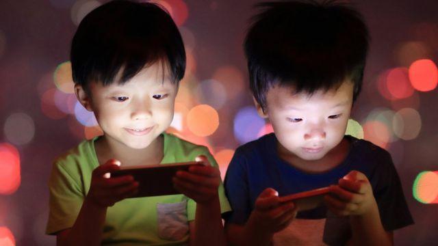 Niños jugando con celular