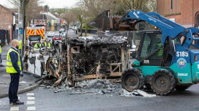 A worker sees a burnt vehicle being carried away by a machine