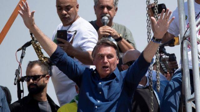 Bolsonaro com as mãos levantadas para o ar