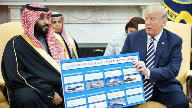 Donald Trump (der.) sostiene un cartel con la descripción de las ventas de armas junto al príncipe heredero de Arabia Saudita, Mohammed bin Salman, en la Casa Blanca, 20 de marzo de 2018