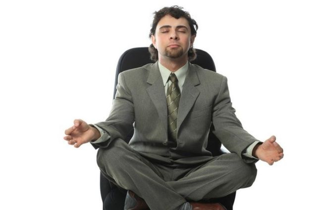 Una persona en pose de meditación en una silla de la oficina