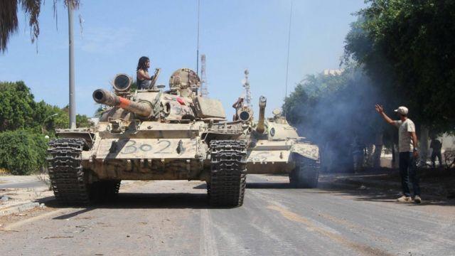 دبابة و مقاتل يقف فوقها ليحيي مسلحين آخرين