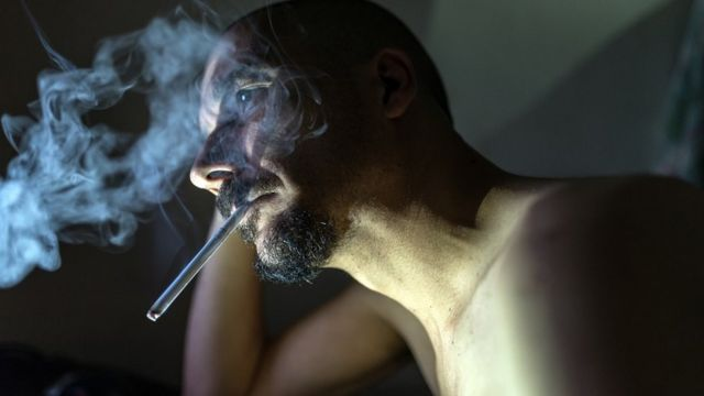 Bearded man smoking, staring vacantly into the distance