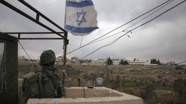 جندي إسرائيلي يحرس مستوطنة بالضفة الغربية