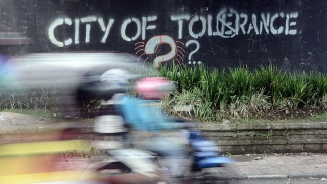 Di sebuah dinding jalan tertulis city of tolerance disertai tanda tanya.