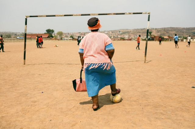 A woman stands on a sandy football pitch