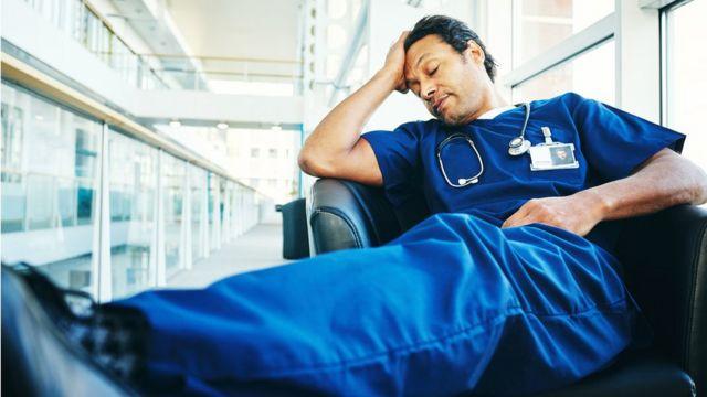 Médico cansado dorme em uma cadeira de hospital