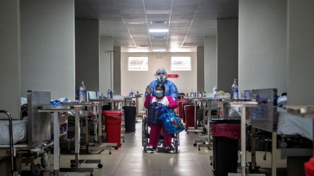 Un paciente de covid trasladado en silla de ruedas en Perú
