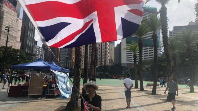 """香港示威者口中的""""王婆婆"""",在游行起步点维多利亚公园挥舞英国国旗。她在一连串的反《逃犯条例》示威中经常出现。"""