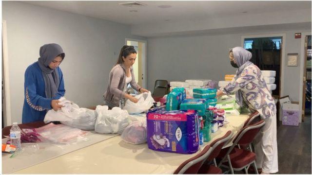 زنان و دختران جوان بدون حجاب اسلامی برای کمک به جابهجایی و طبقهبندی اجناس اهدایی به مسجدی در آمریکا آمدند